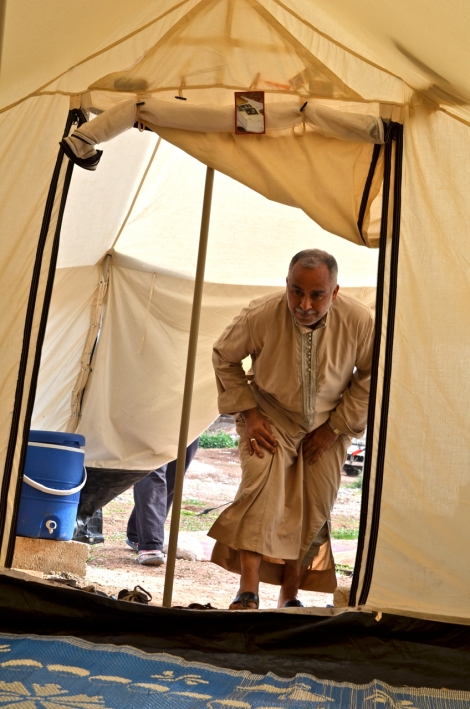 Asad Hoammed enters his UN refugee tent, his home since fleeing Tall-Rifat late February.